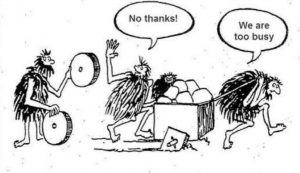 Cartoon of stoneage men being too busy to accept the offer of round wheels for their cart with square wheels on!